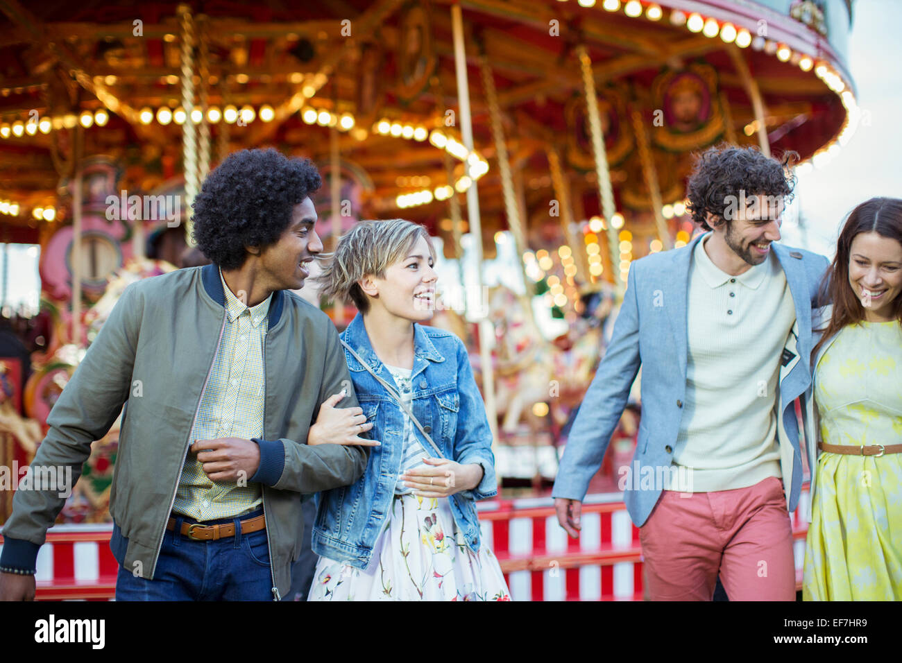 Two couples walking in amusement park and laughing - Stock Image