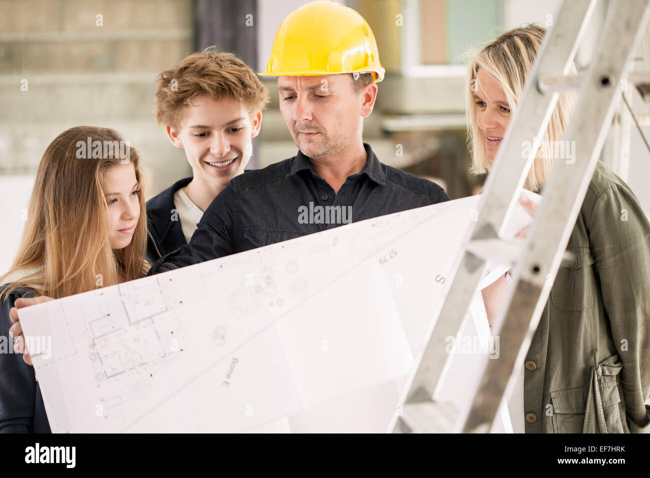 Engineer showing blueprint to family - Stock Image