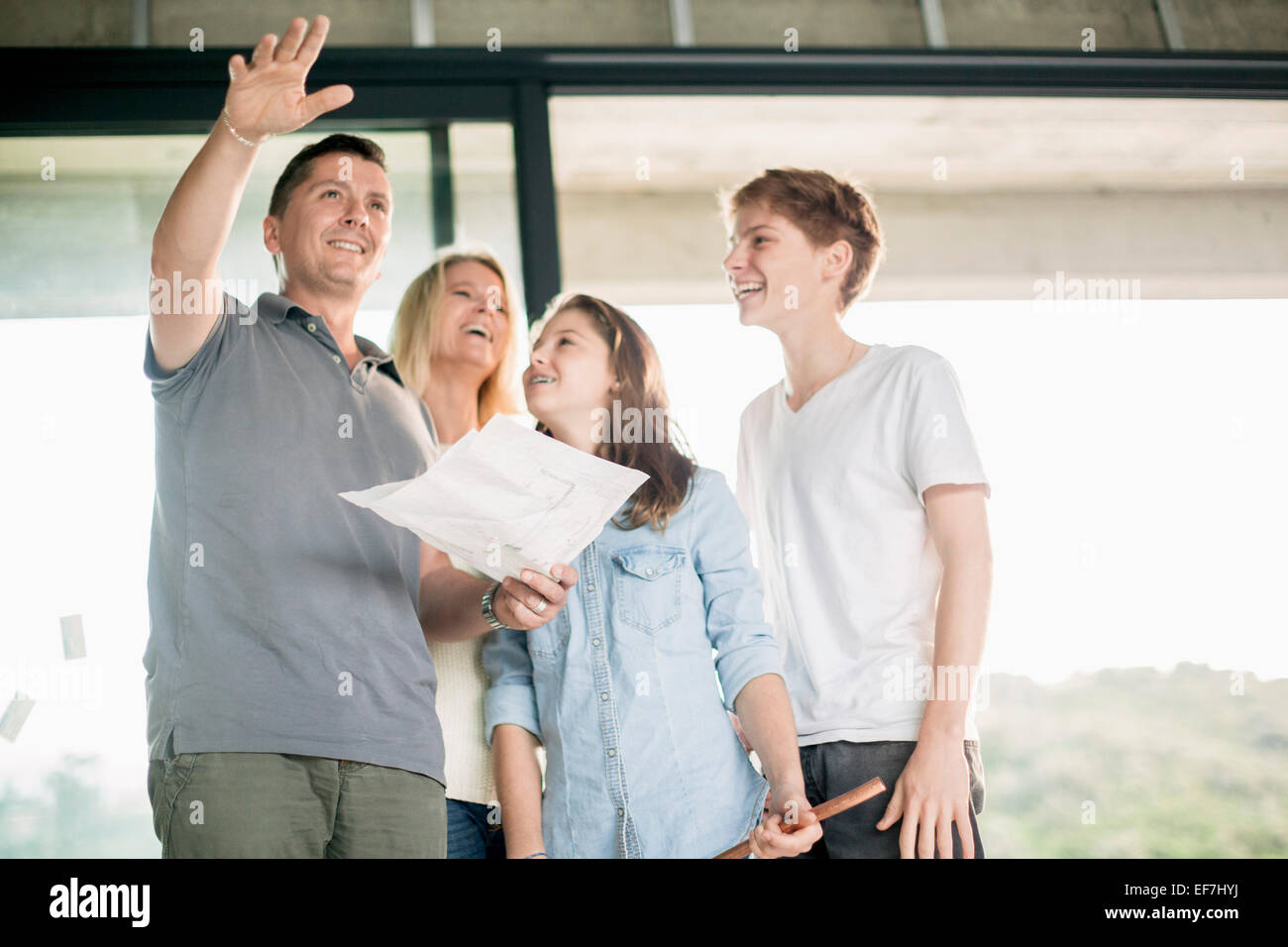 Family discussing blueprint at home - Stock Image