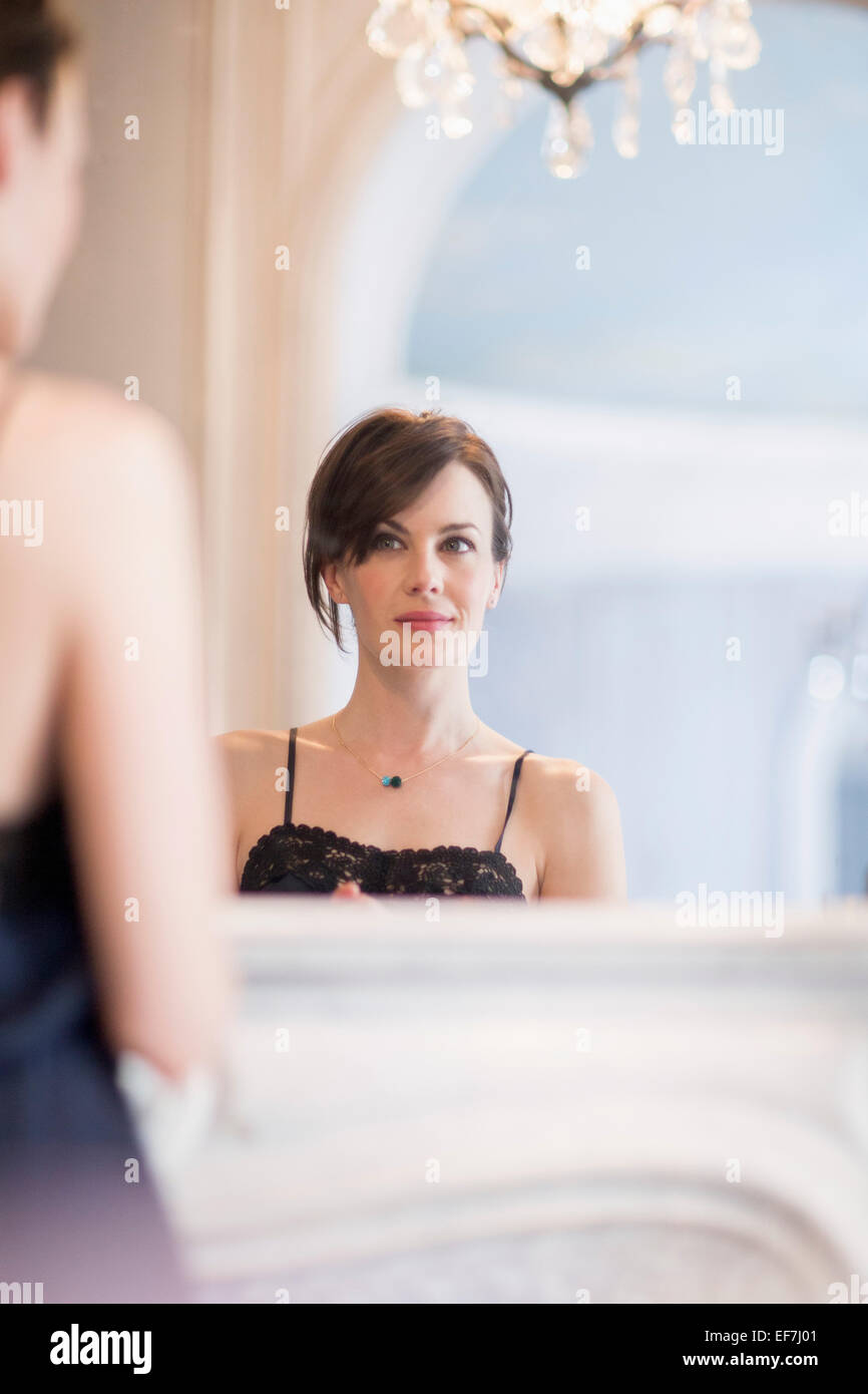 Reflection of a woman in mirror - Stock Image