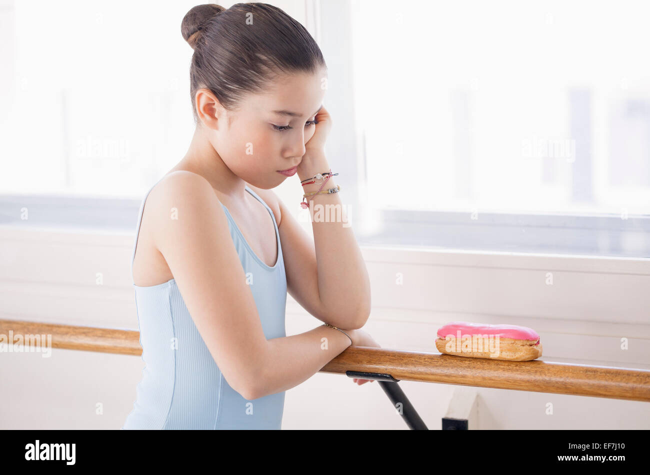 Girl looking displeased with eclair Stock Photo