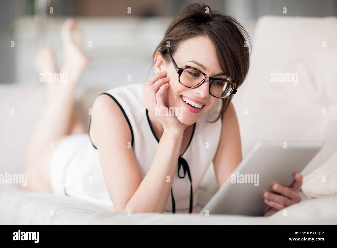 Woman lying on the bed and looking at a digital tablet - Stock Image