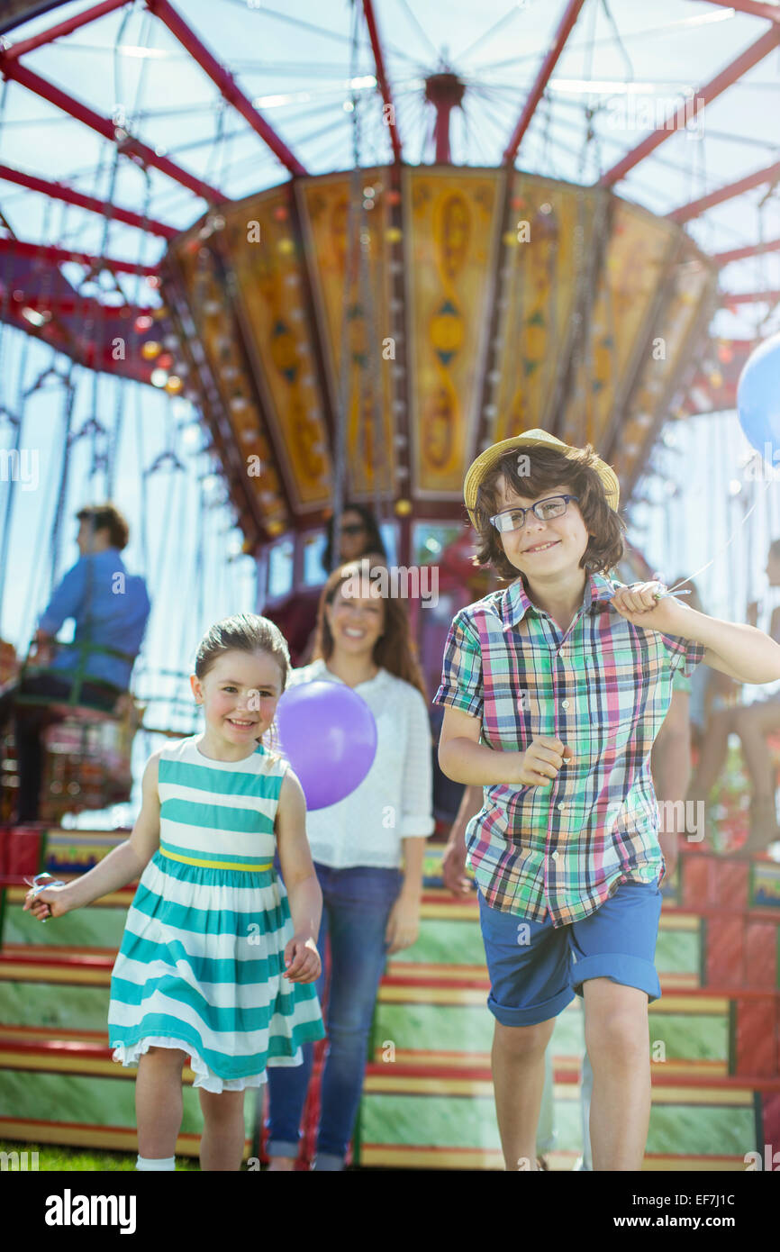 Children running in front of carousel, mother following them Stock Photo