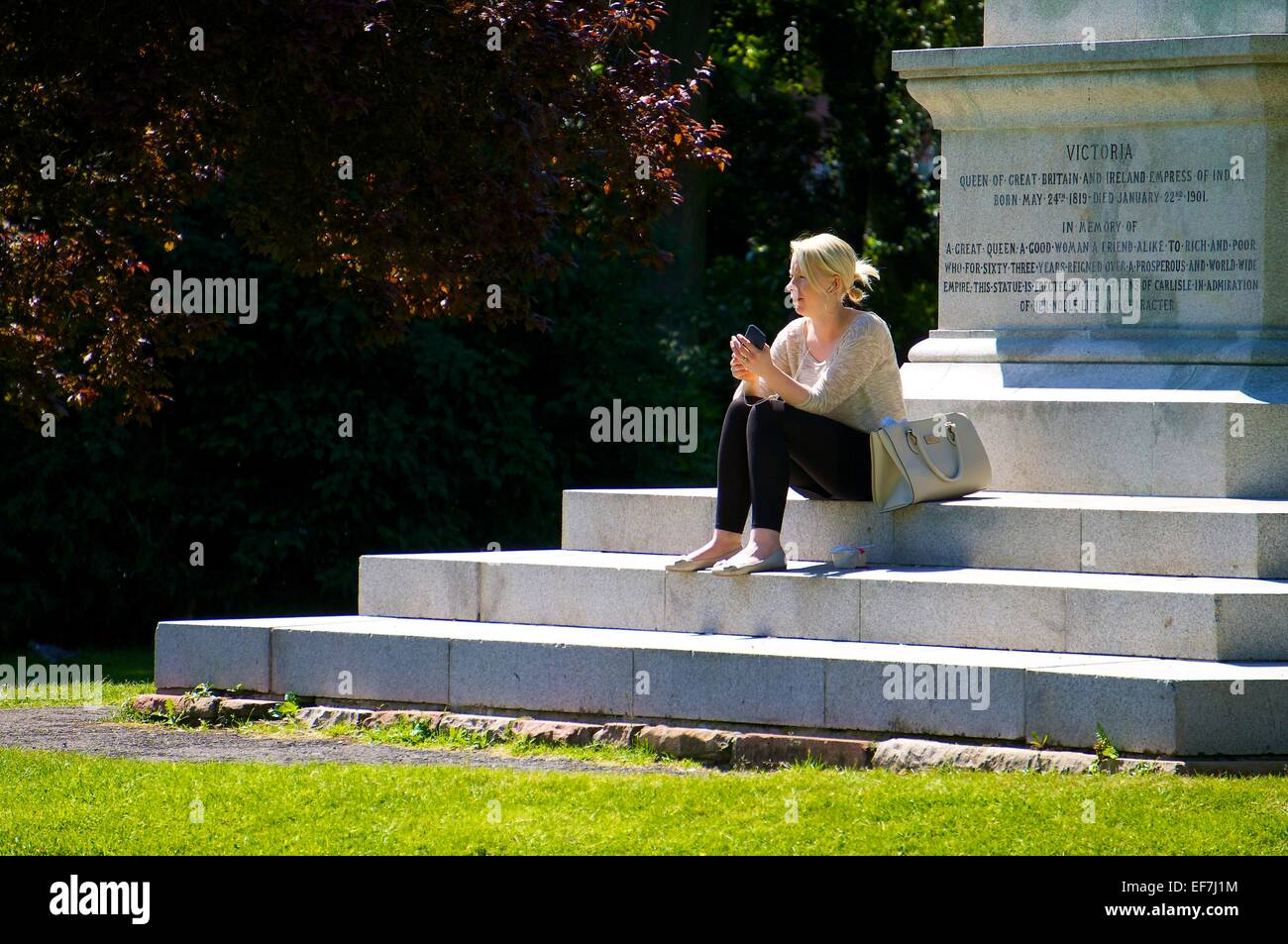 Woman listening to her music on a smart phone while siting on the steps of a monument. - Stock Image