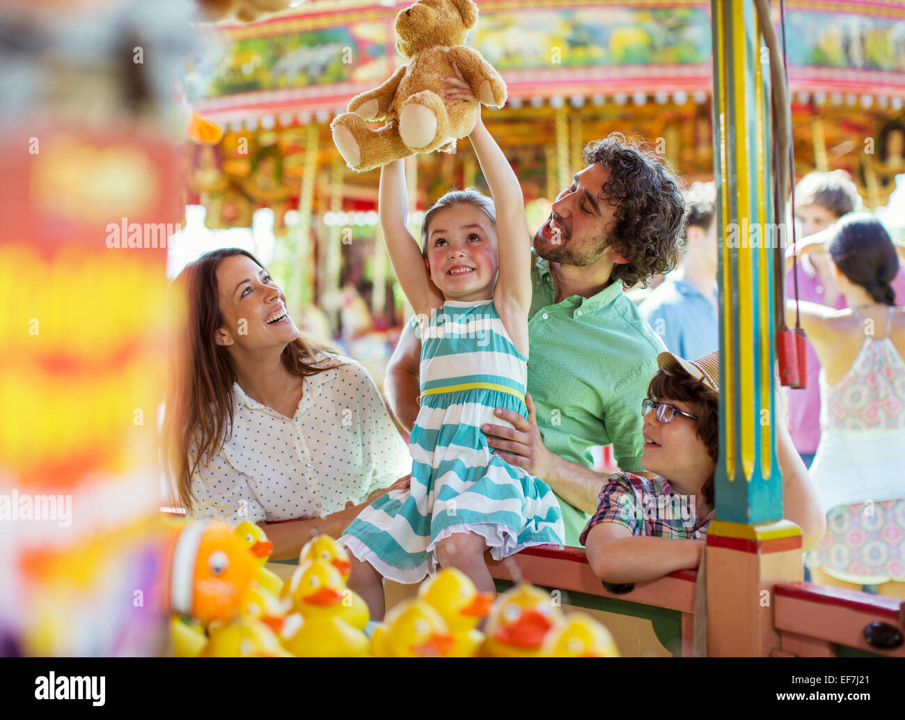 Girl holding teddy bear as trophy in fishing game in amusement park - Stock Image