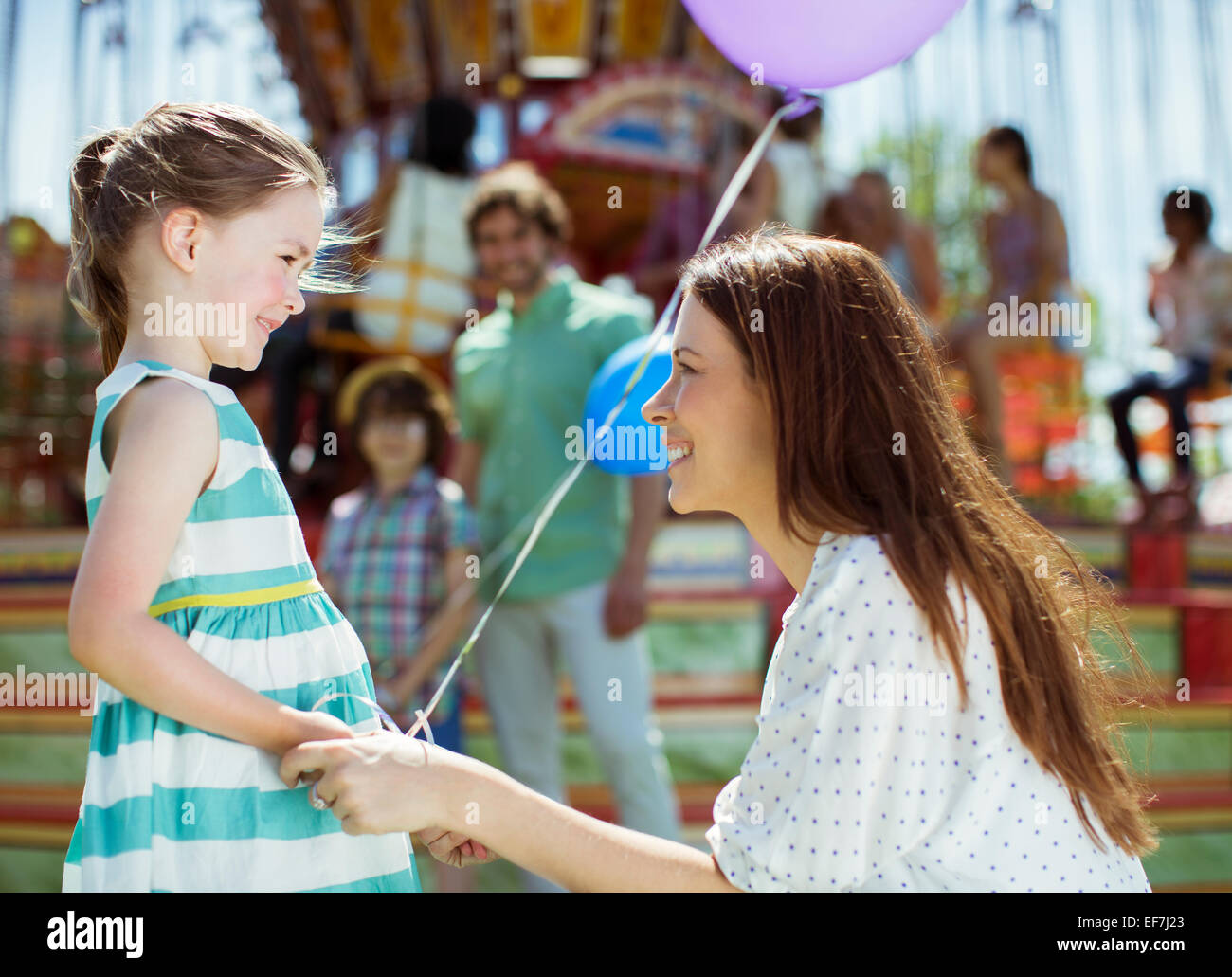Mother and girl with balloon looking at each other in amusement park - Stock Image