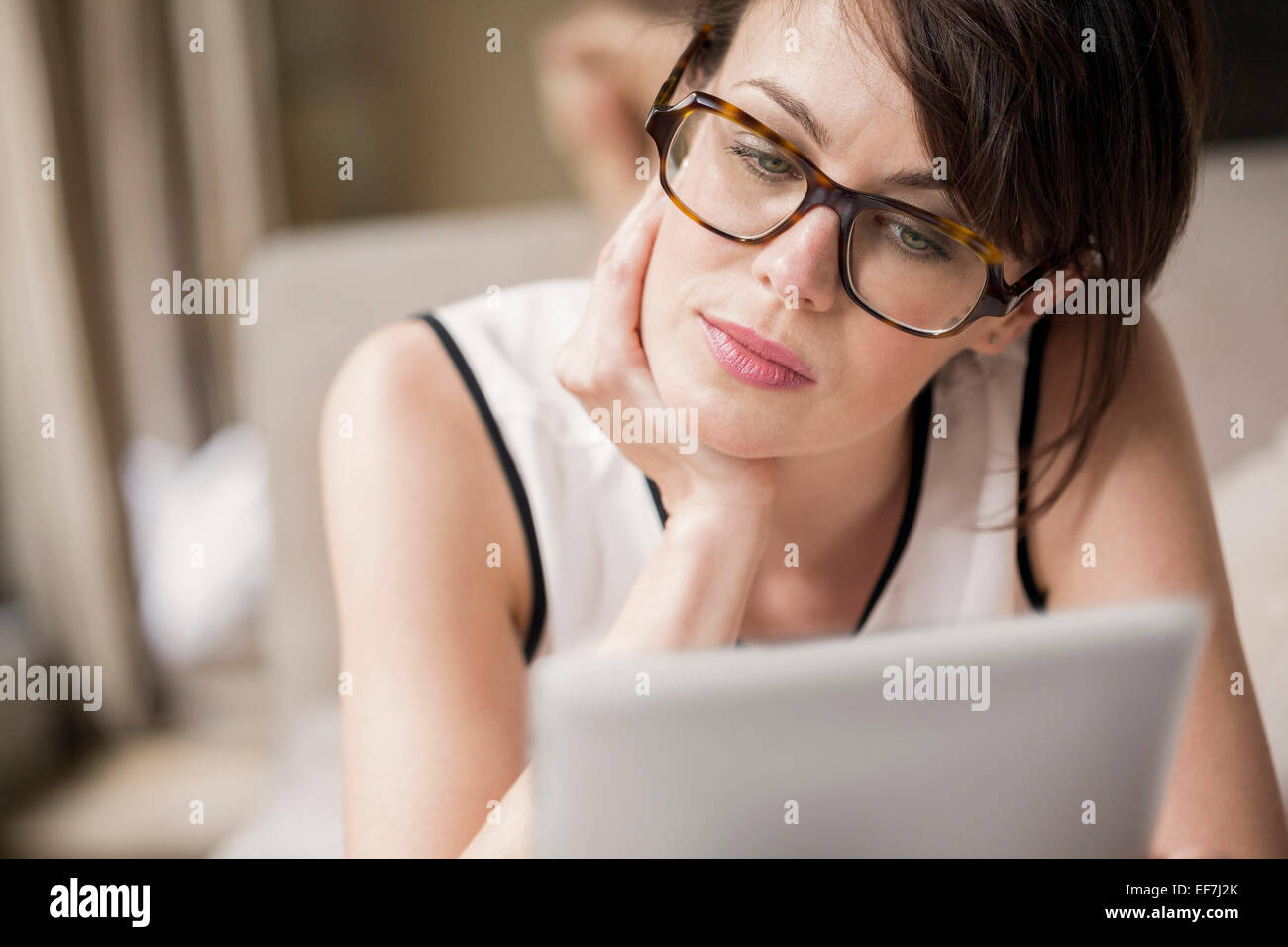 Woman lying on the bed and looking at a digital tablet Stock Photo
