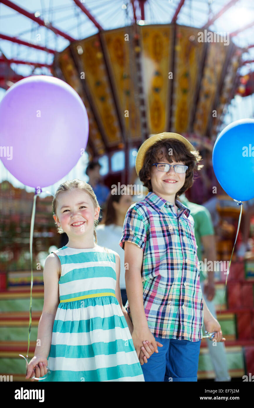Portrait of boy and girl holding balloons in amusement park - Stock Image