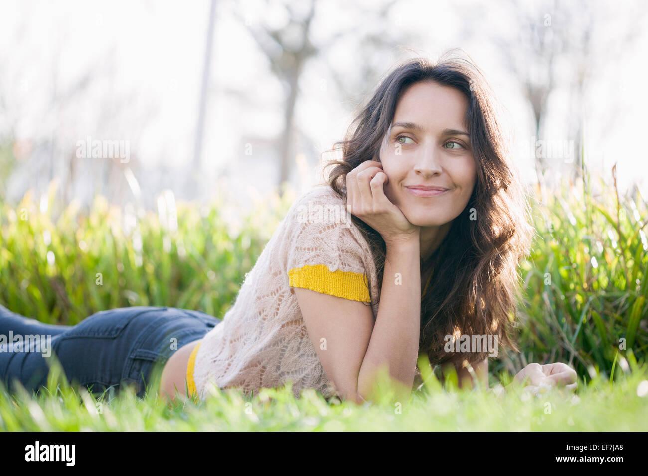 Happy beautiful woman lying on the grass Stock Photo