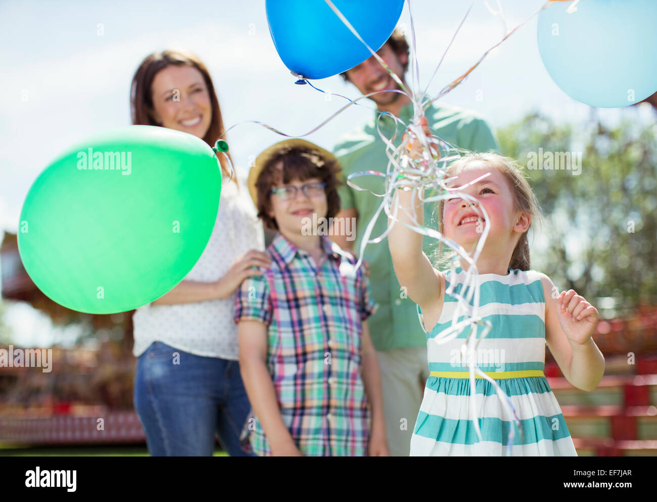 Young girl holding bunch of balloons, family standing behind her - Stock Image