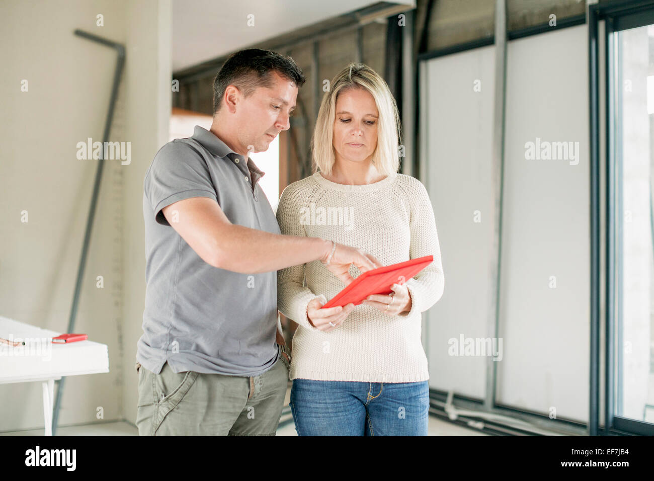 Couple using digital tablet at home - Stock Image