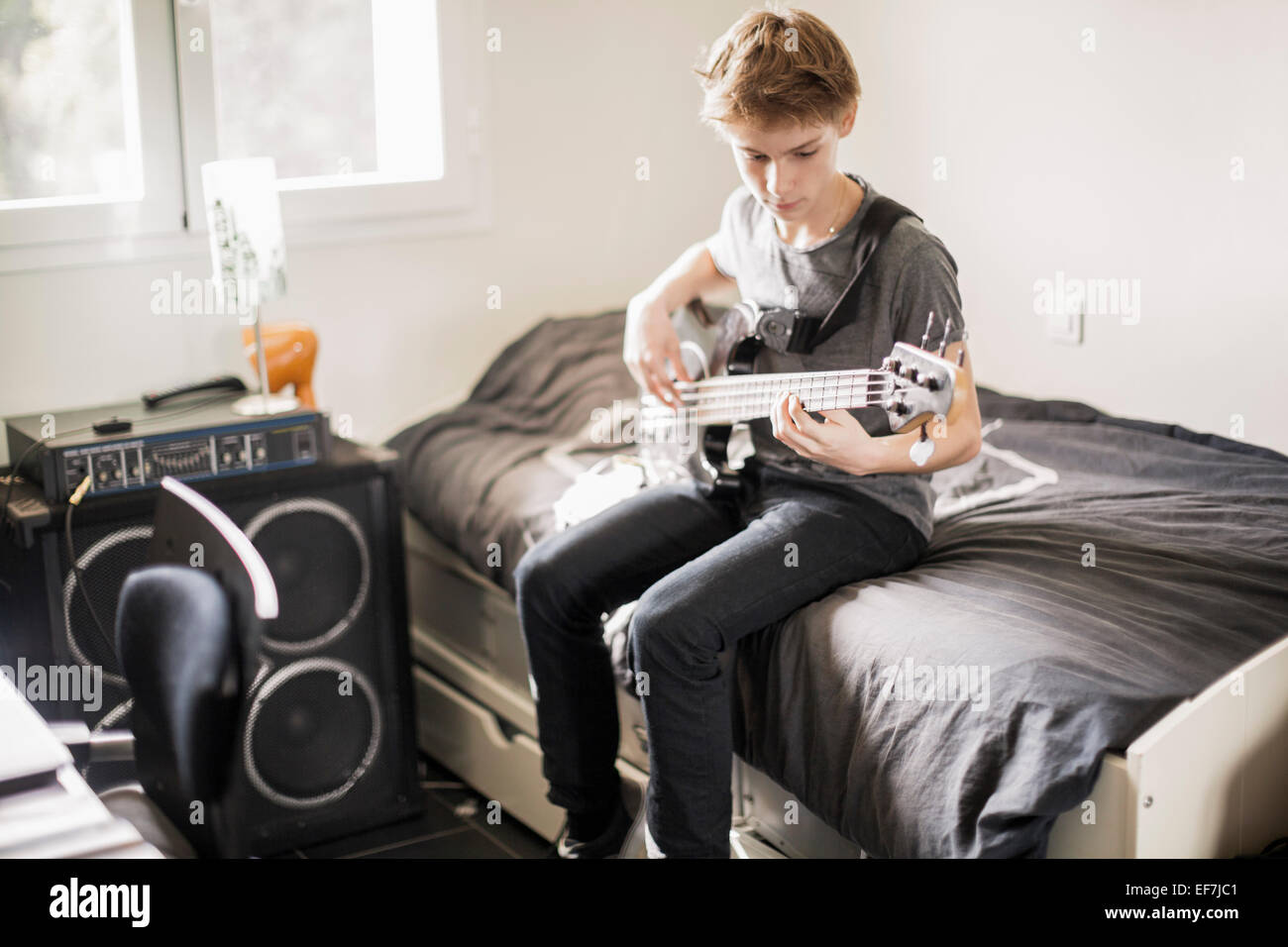 Teenage boy playing a guitar on bed - Stock Image