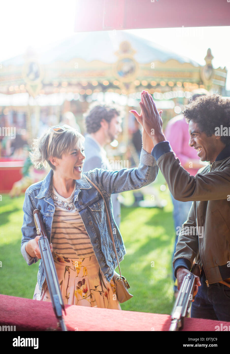 Young couple giving high five in amusement park Stock Photo