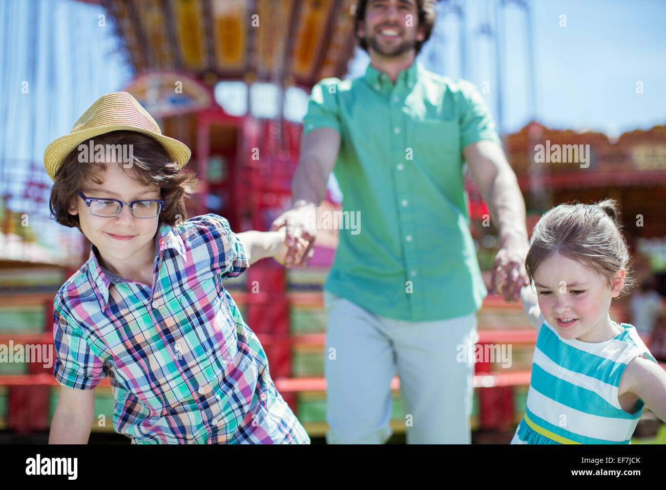 Girl and boy pulling their father in amusement park - Stock Image