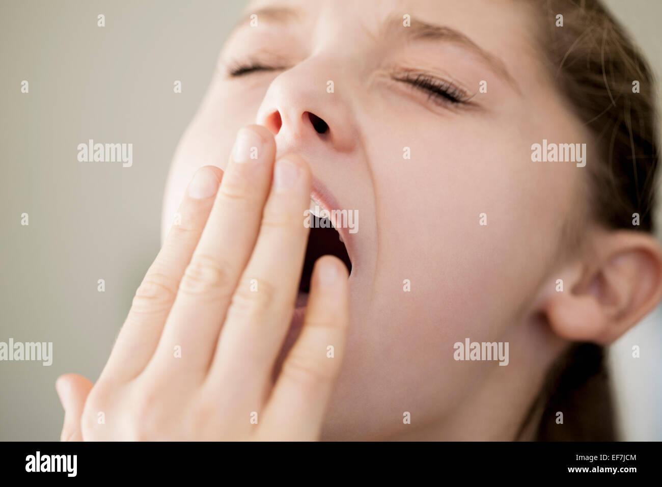 Close-up of a girl yawning - Stock Image
