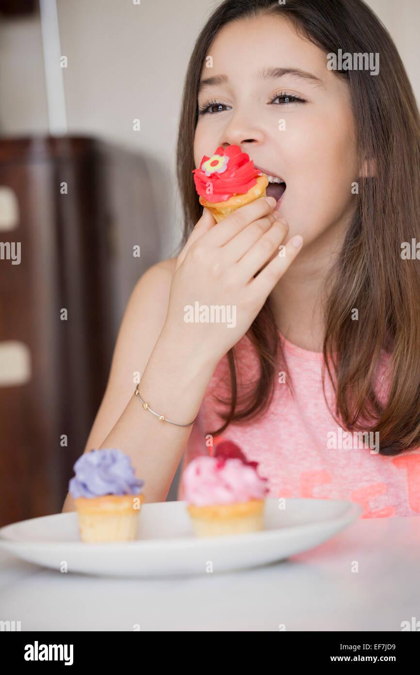 Happy girl eating cupcake - Stock Image