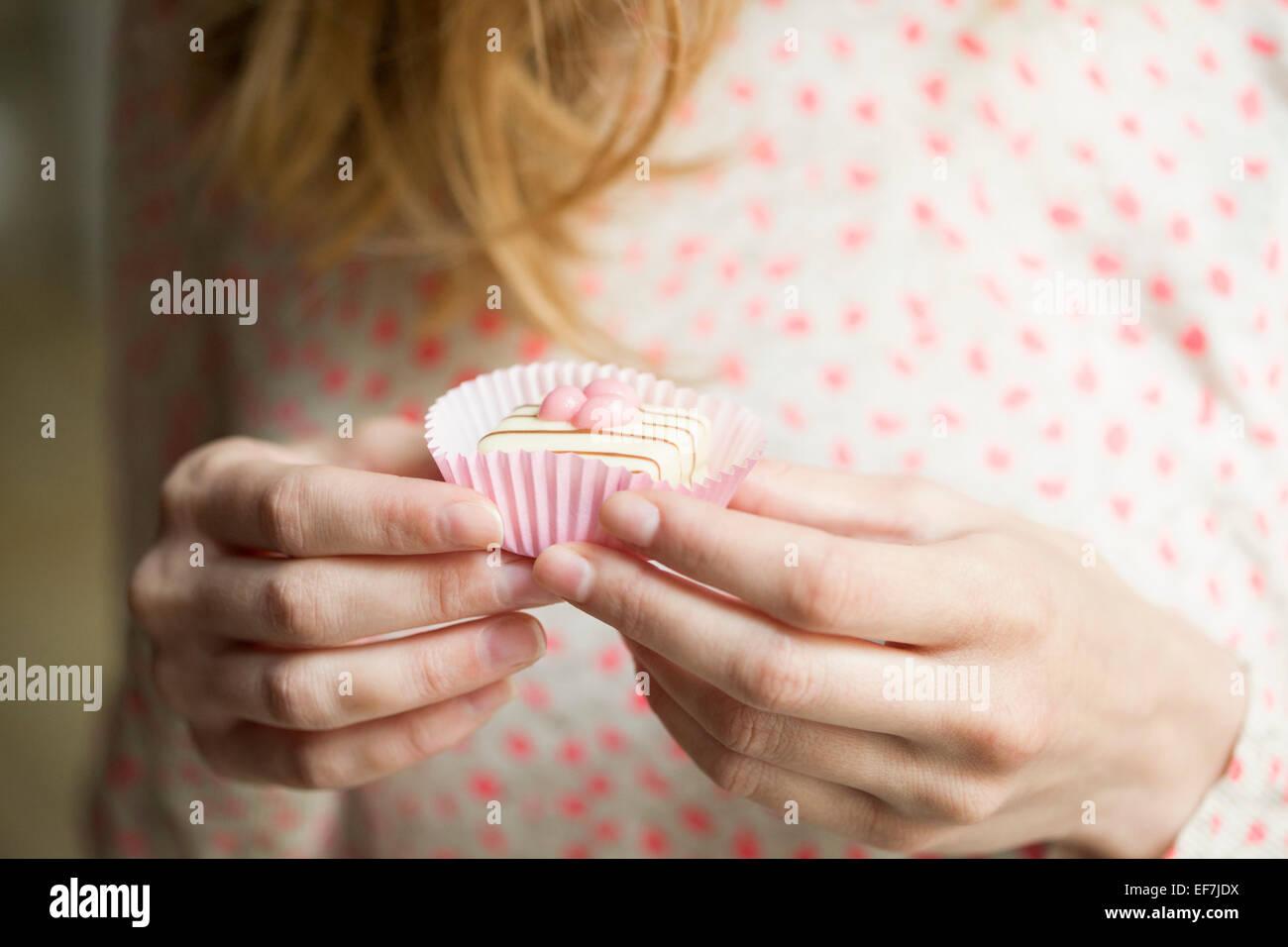 Woman eating a cupcake - Stock Image