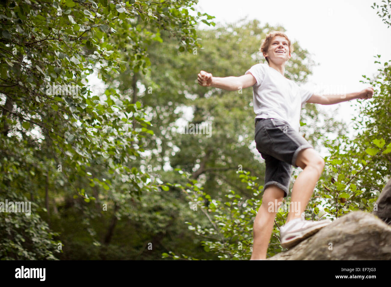 Teenage boy playing in a park - Stock Image