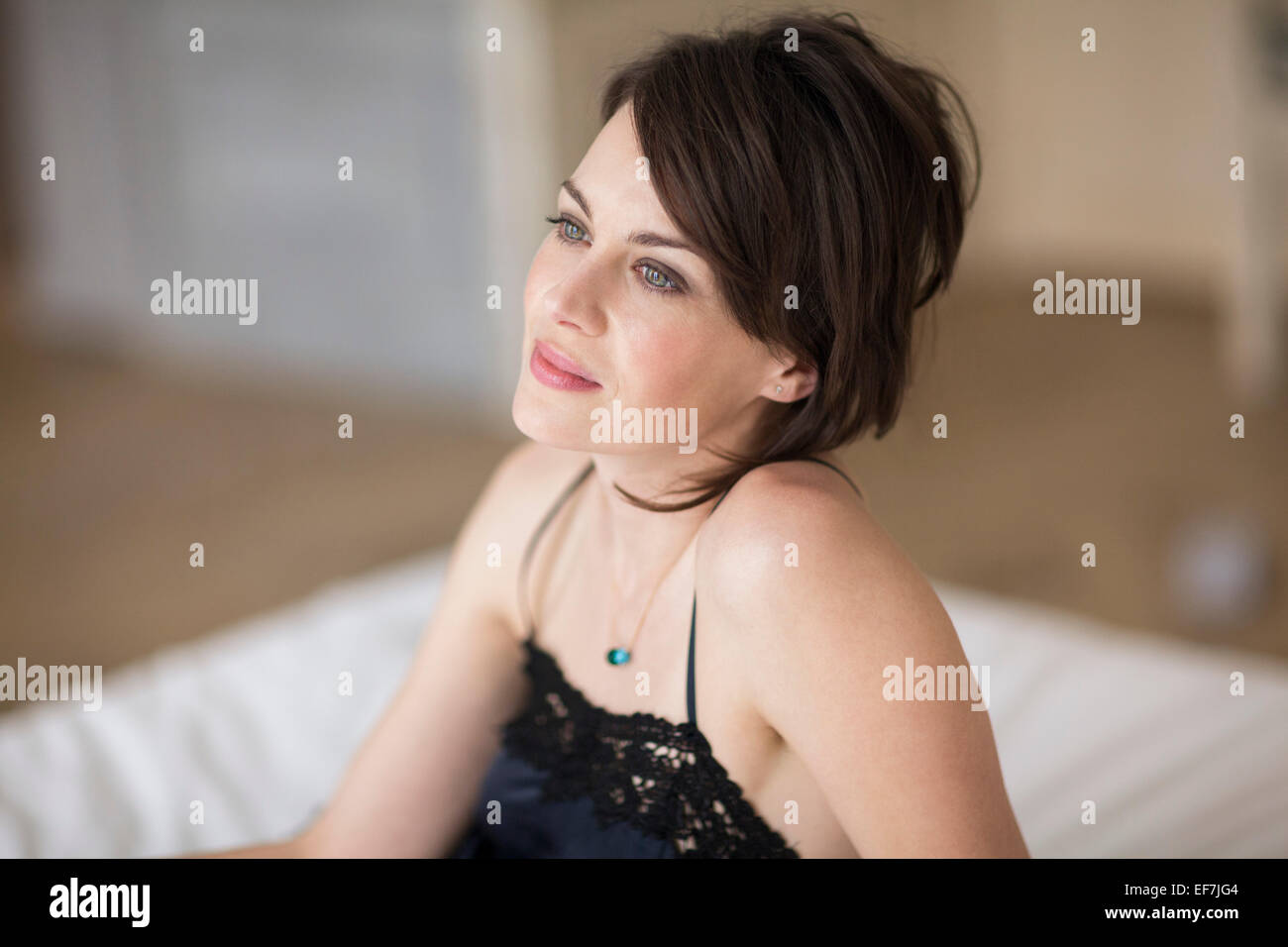 Beautiful woman sitting on the bed - Stock Image