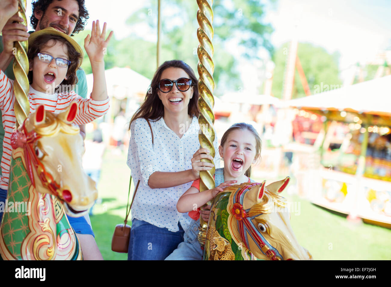 Family on carousel in amusement park - Stock Image