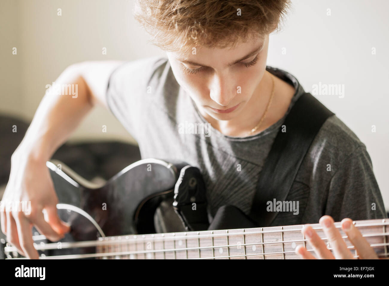Teenage boy playing a guitar - Stock Image