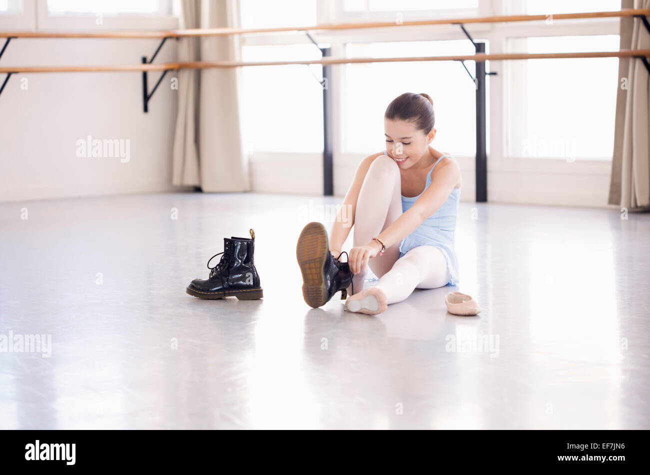 Girl putting on shoe in health club - Stock Image