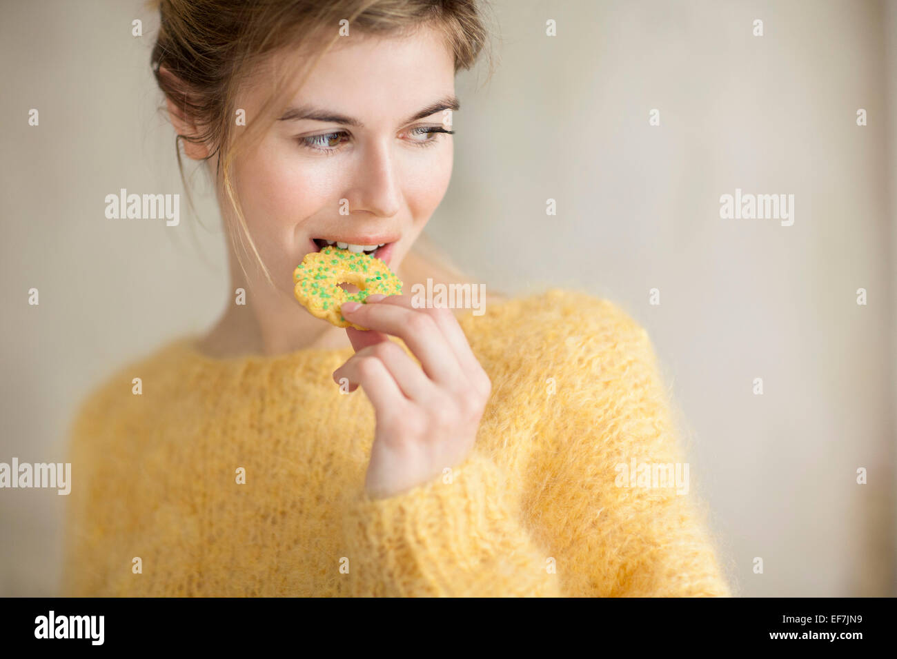 Woman eating a cookie - Stock Image