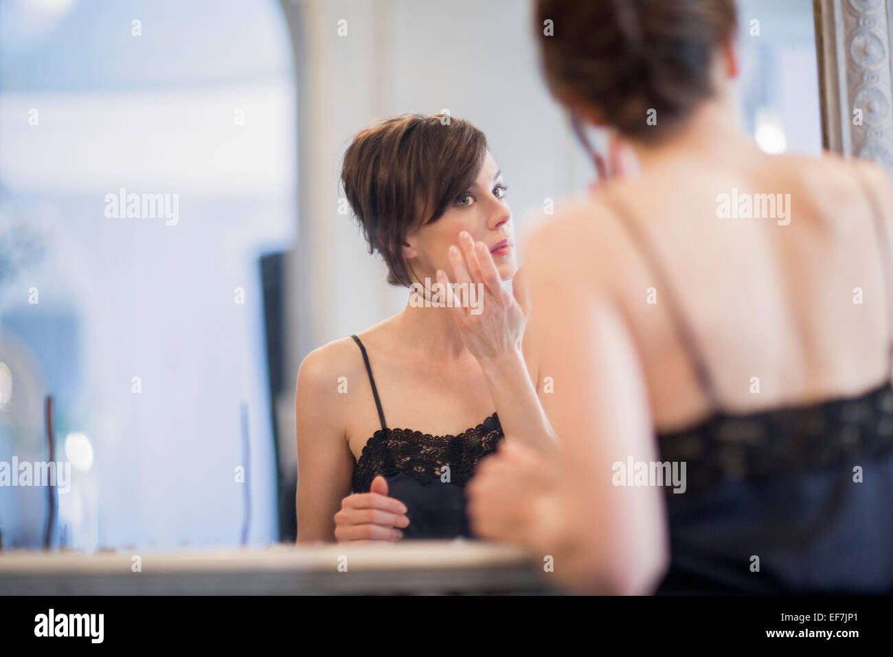 Woman applying anti-aging cream on her face - Stock Image