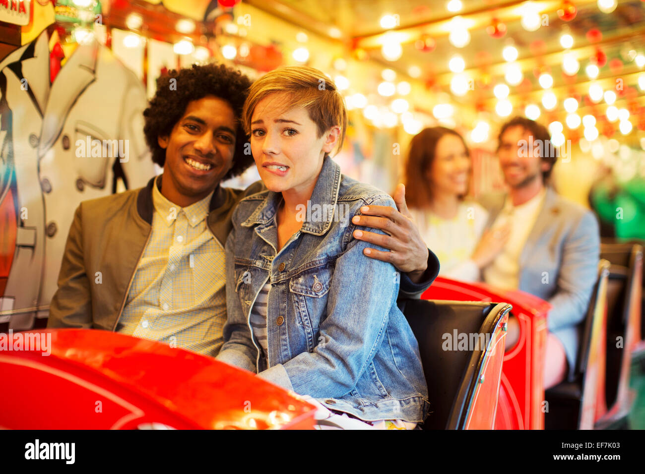 Man embracing scared girlfriend on ghost train - Stock Image