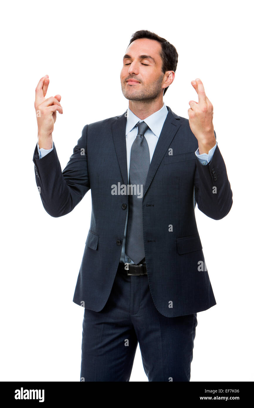 Half length portrait of a businessman with eyes closed and fingers crossed - Stock Image