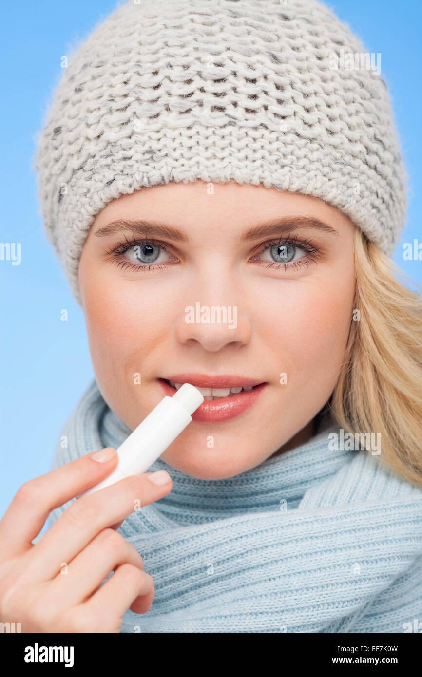 Beautiful woman applying lip balm - Stock Image
