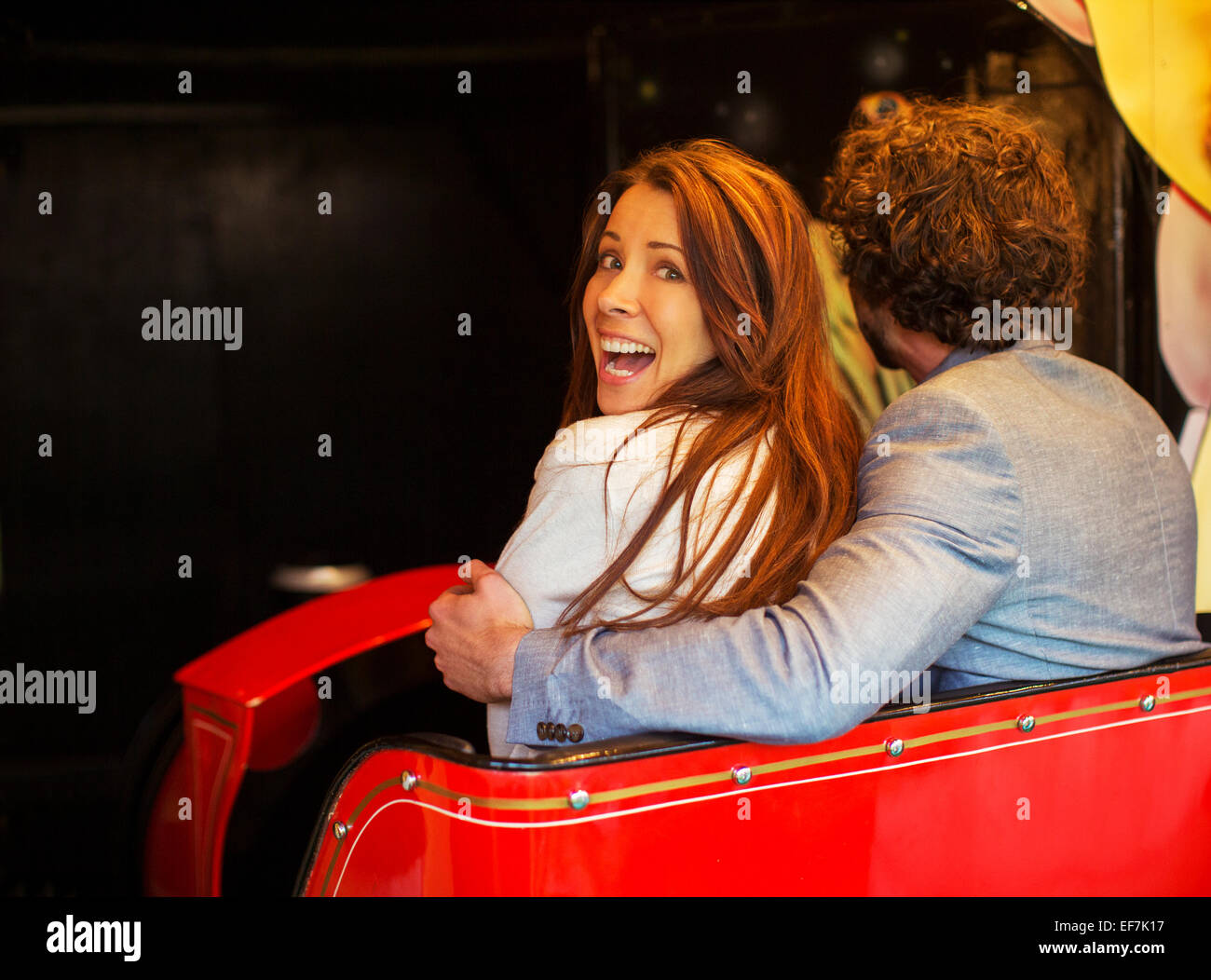Man embracing scared girlfriend while going into tunnel in ghost train - Stock Image