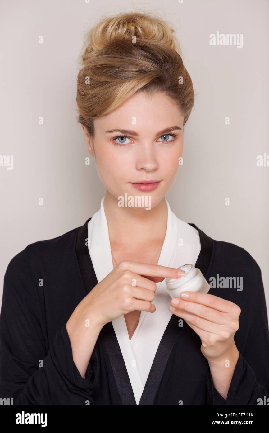 Portrait of beautiful woman applying moisturizer - Stock Image