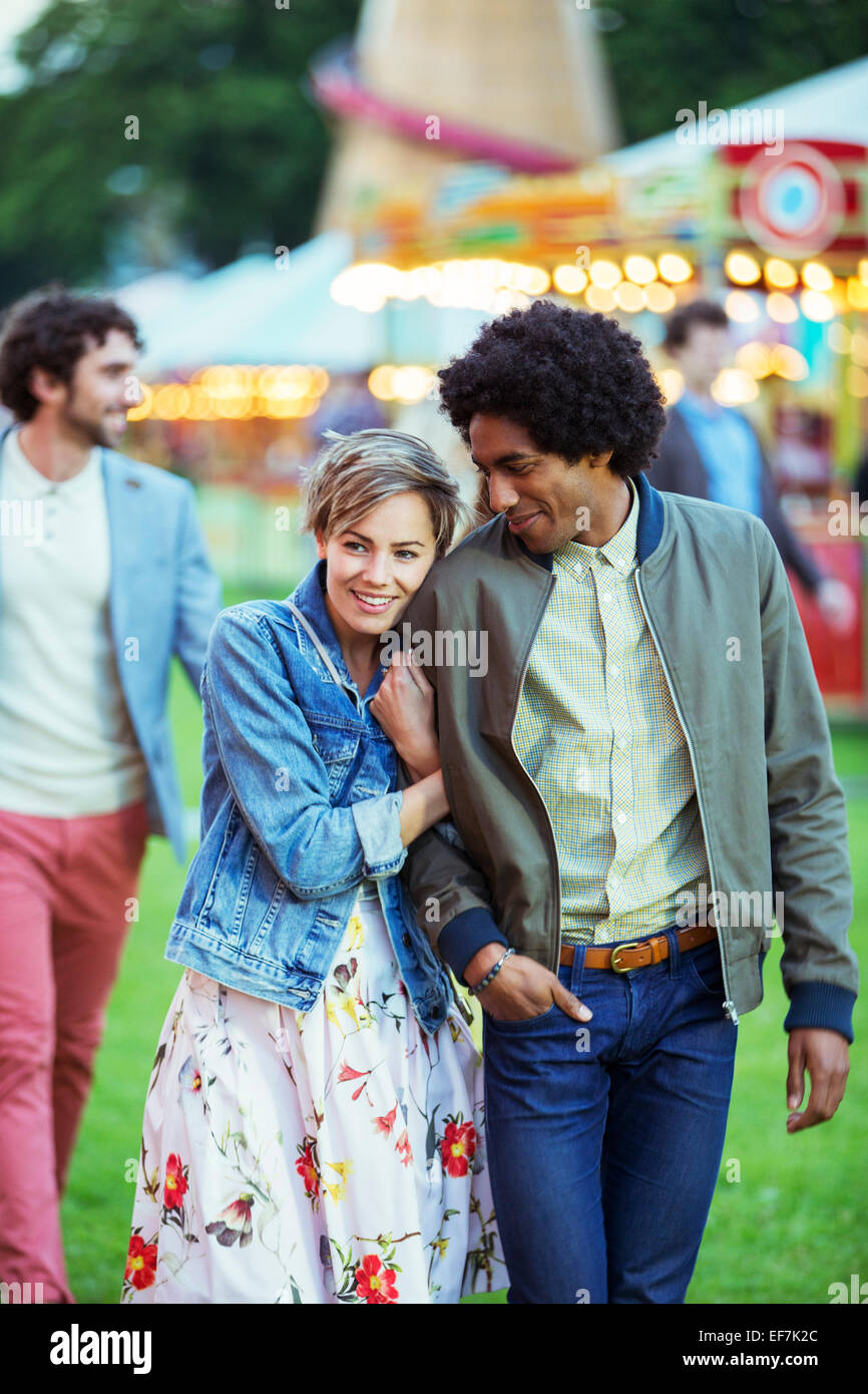 Young multiracial couple smiling in amusement park - Stock Image