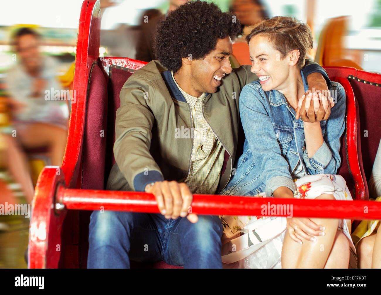 Cheerful couple on carousel in amusement park Stock Photo