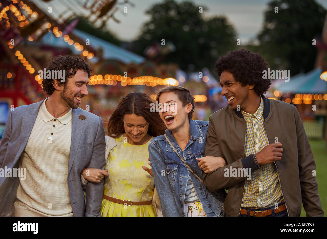 Two couples walking in amusement park and laughing at dusk - Stock Image