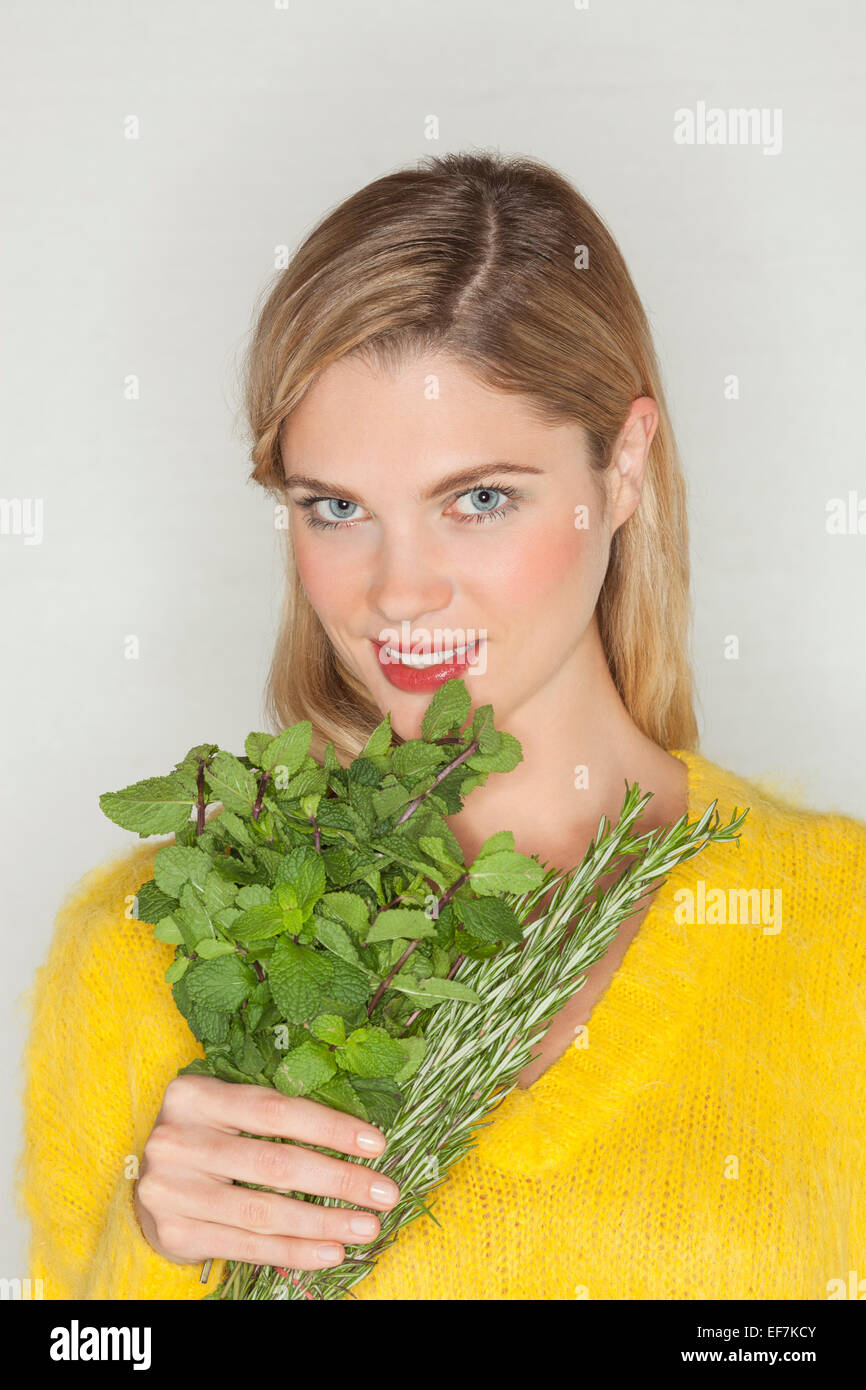 Portrait of a beautiful woman holding herbal leaves Stock Photo