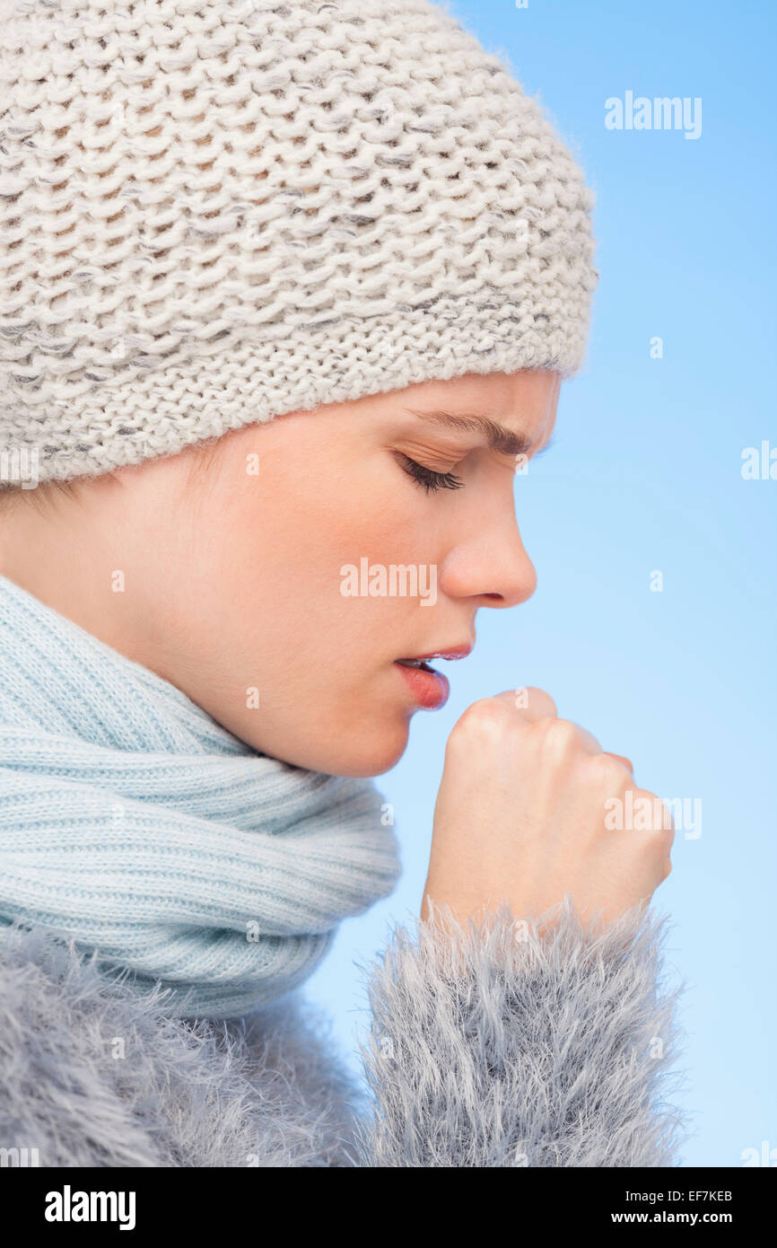 Woman in knitted hat and coughing - Stock Image