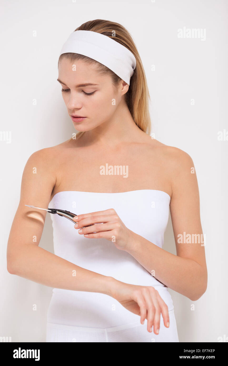 Beautiful woman examining her skin with magnifying glass - Stock Image