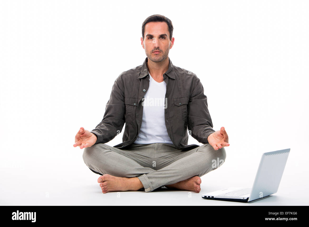 Man sitted on the floor looking at the camera and practicing yoga with laptop next to him - Stock Image