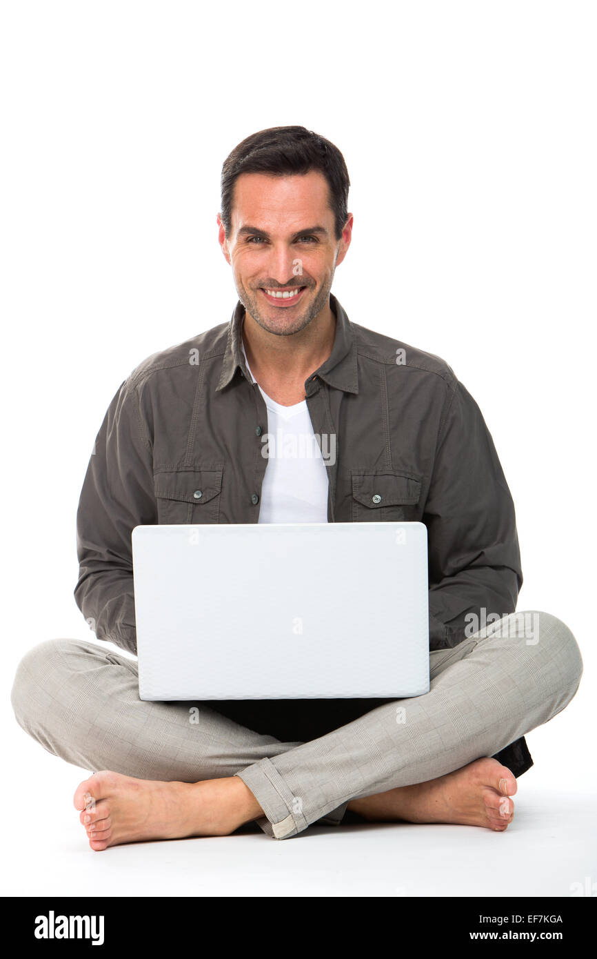 Man sitted on the floor, smiling at camera and working with his laptop - Stock Image