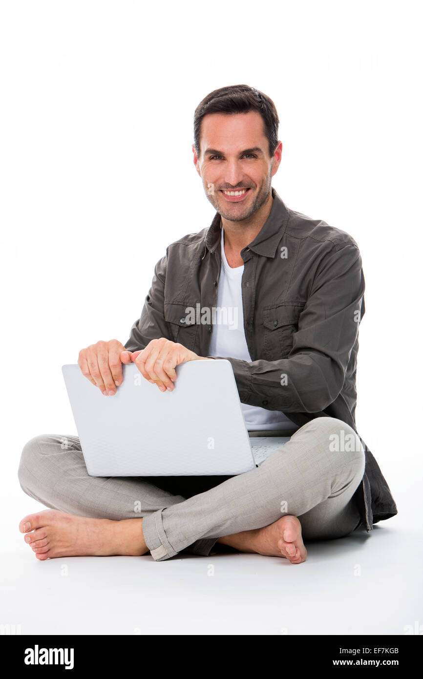 Man sitted on the floor, smiling at camera, holding his laptop with both hands - Stock Image