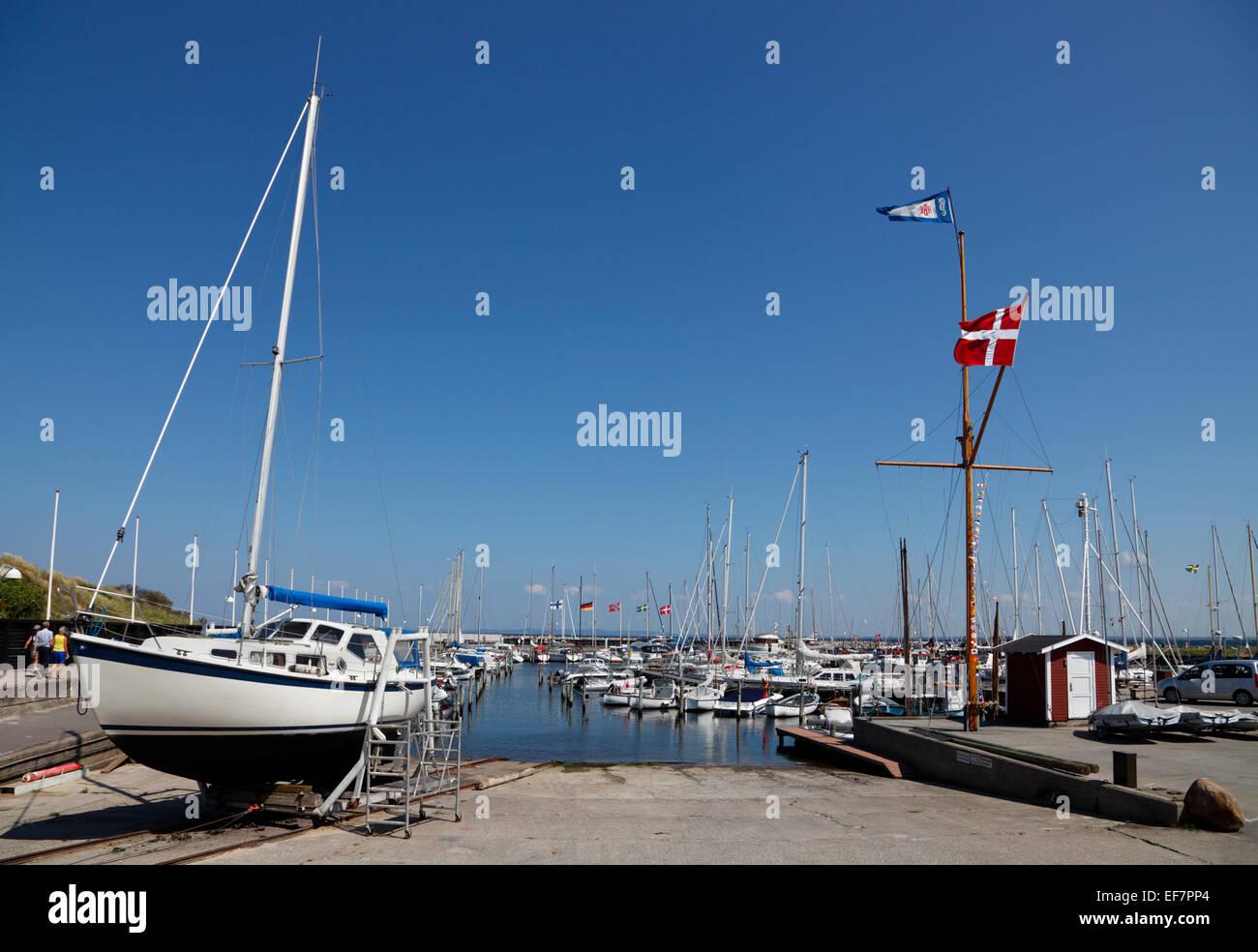 Hornbæk / Hornbaek Harbour, North Zealand, Denmark, on a warm and sunny summer day. A sailing boat still on - Stock Image