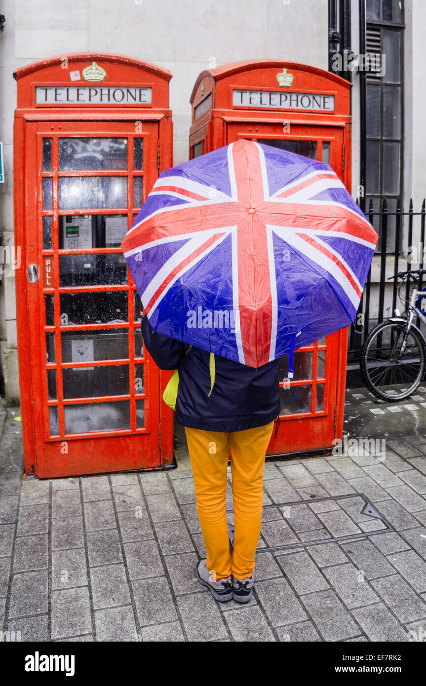 Women with Umbrella , Red Telephone Box, London, United Kingdom - Stock Image