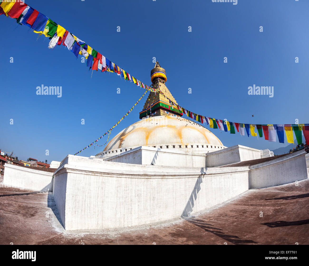 Bodhnath stupa with colorful prayer flags at blue sky in Kathmandu valley, Nepal - Stock Image