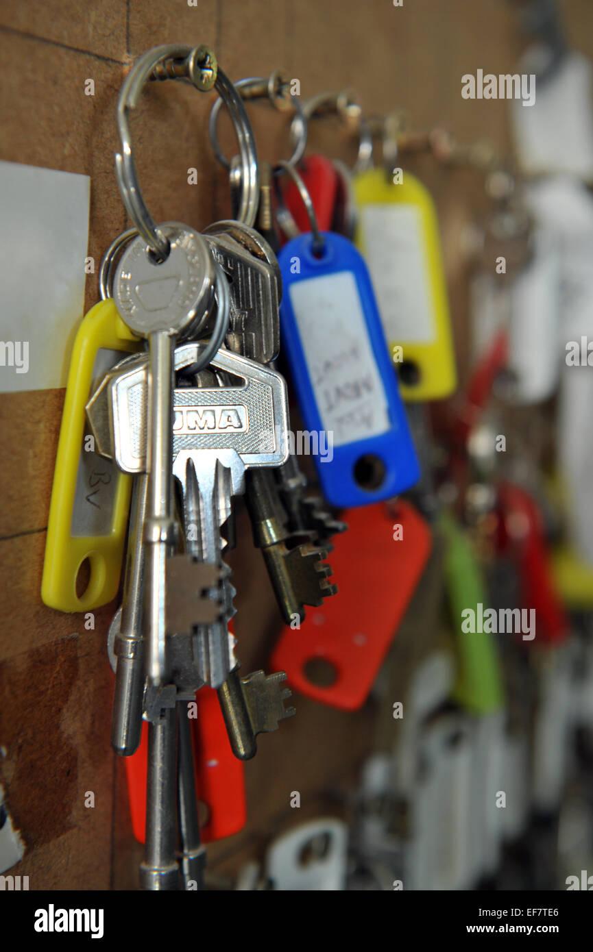 Housing Association keys for tenants flats hung on a peg. - Stock Image