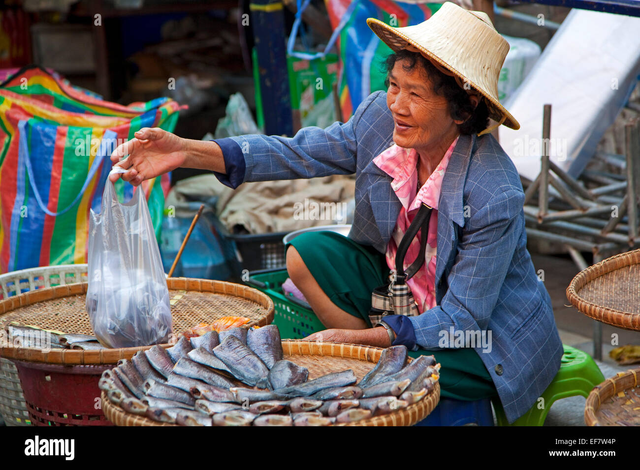 Elderly Thai woman with traditional palm wicker hat selling fish at food market in Ayutthaya, Thailand - Stock Image