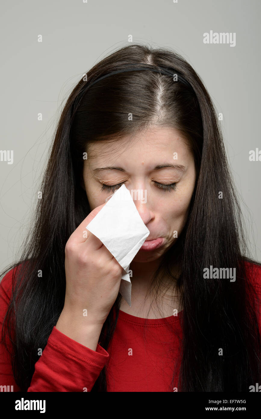 Woman crying and wiping her tears with a paper tissue - Stock Image