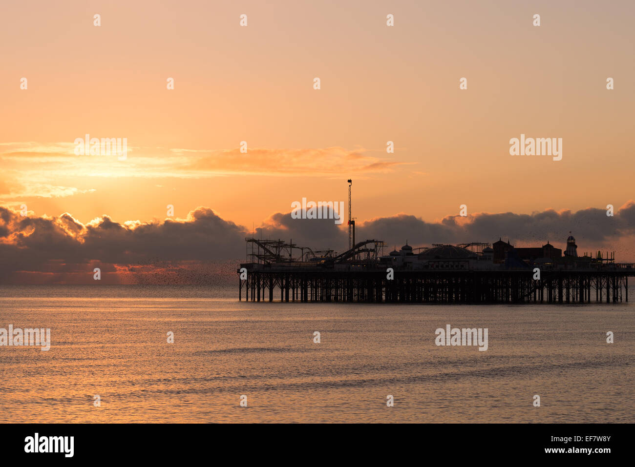 Setting sun behind the silhouette of the Palace Pier Stock Photo