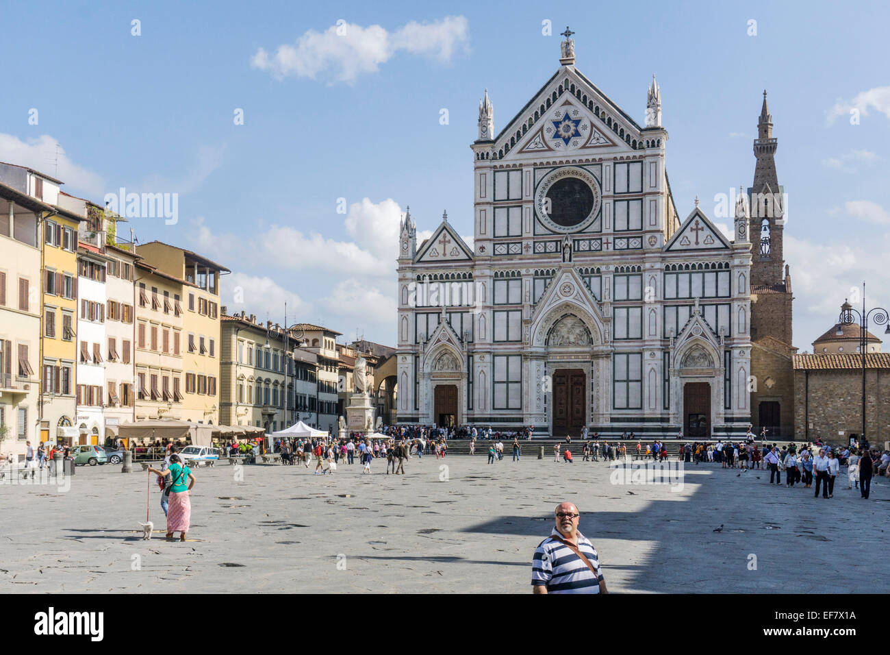 street scene people crowd piazza of magnificent Renaissance Franciscan basilica Santa Croce with neo Gothic facade - Stock Image